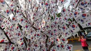 A woman takes a photograph of a tree decorated with national flags at the national cemetery in Seoul