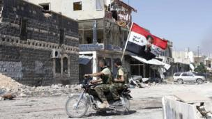 Forces loyal to Syria's President Bashar al-Assad carry the national flag as they ride on a motocycle in Qusair, after the Syrian army took control from rebel fighters on 5 June 2013