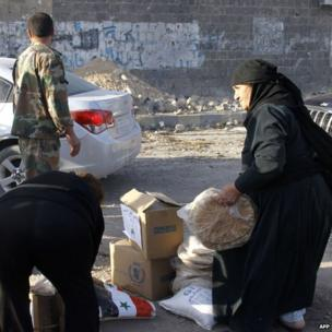 Syrian residents of Qusair receive food provided by the Syrian government after the regime's forces seized total control of the city