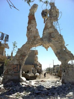 The remains of a building with Syrian army soldiers walking in a street left in ruins on 5 June in the city of Qusair