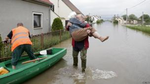 A resident carries a woman as they leave a flooded street in the Czech village of Nove Kopisty June 6, 2013