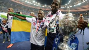 Malian forward Cheick Diabate (R) holds the trophy beside Senegalese defender Ludovic Lamine Sane after winning the French Cup Final football match between Bordeaux and Evian at the Stade de France in Paris - Friday 31 May 2013