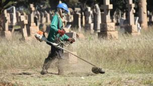 A council worker cutting grass in a cemetery, Harare, Zimbabwe - Tuesday 4 June 2013