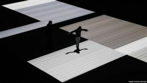 A woman plays with her shadow on top of Test Pattern, an installation by Japanese artist Ryoji Ikeda at the Vivid Festival in Sydney, Australia