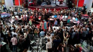The Queen surrounded by journalists in the BBC newsroom.