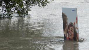 A sign is engulfed by flood water