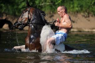 A traveller washes his horse in the waters of the River Eden in preparation for selling at the Appleby Horse Fair