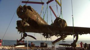 The rusted plane, missing part of a wing, held up by a crane