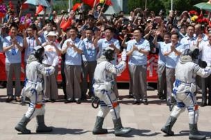 Chinese astronauts, Wang Yaping, Zhang Xiaoguang and mission commander Nie Haisheng wave to onlookers