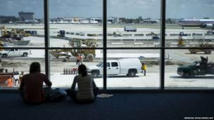 People watch construction workers at Miami International Airport
