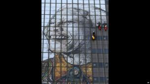 Workers put up a portrait of Nelson Mandela on the windows of a building in Cape Town, South Africa - Thursday 13 June 2013