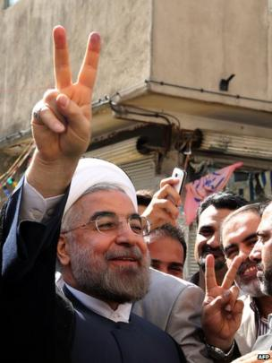 Iranian moderate presidential candidate, Hassan Rouhani flashes the sign of victory as he leaves a polling station after voting on June 14.