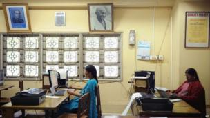 Employees feed in telegram messages onto computers to be sent via telegraph at a telecommunications office in Bangalore