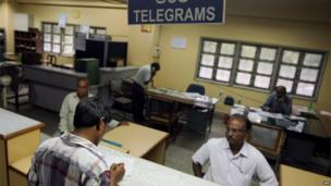 A customer (foreground L) fills in a form for sending out a message using the telegraphic service at a telecommunications office in Bangalore