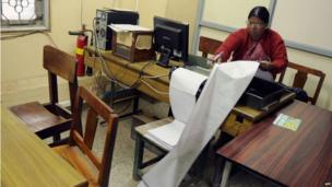 An employee sorts incoming telegrams printed on a continuous sheet of paper at a telecommunications office in Bangalore on June 13, 2013