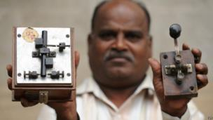 An employee displays an antique telegraph transmitter key (R), which the operator uses to send messages using Morse code, and a telegraph receiver (L) at a telecommunications office in Bangalore on June 13, 2013