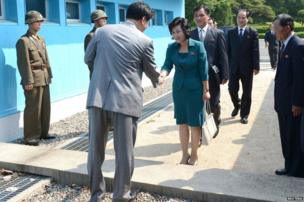 A South Korean official greets the North Korean delegation for inter-Korean talks, at Panmunjom
