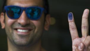 An Iranian national shows his finger covered in ink after voting at the Iran Interests Section office in Washington