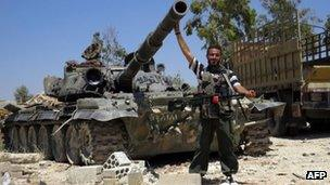 A Syrian rebel fighter poses in front of a tank reportedly seized from an army barrack. Photo: June 2013