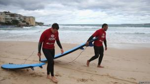 Justin Tipuric and Toby Faletau drag their surfboards back along the beach