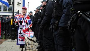 Woman draped in union flag with line of police officers