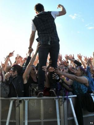 Chris Batten of Enter Shikari stands on the crowd barrier during his performance at the Download festival on Saturday