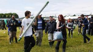 A man carries beer cups during the Download festival on Friday