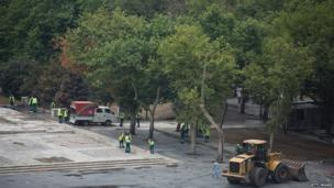 Workers clean Gezi Park after the overnight crackdown against protesters