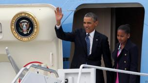 US President Barack Obama waves as he leaves his plane with daughter Sasha.