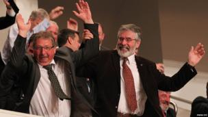 Finance Minister Sammy Wilson and Sinn Fein President Gerry Adams join in a Mexican wave as the gathered crowd await the arrival of President Obama at the Waterfront Hall