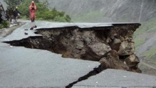 Indian people walk on a road which was caved in after incessant rains on Rishikesh-Mana highway near Joshimath district in northern Indian state of Uttarakhand, India, Monday, June 17, 2013