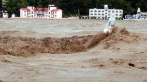 Fast moving water flows over a Hindu statue during a heavy monsoon rain in Rishikesh town in the Indian state of Uttrakhand on June 17, 2013