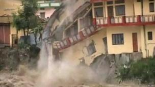 A building starts to collapse into rising water of river Ganga in northern India's pilgrimage town of Uttarkashi in this still image taken from video June 16, 2013, after 36 hours of rain