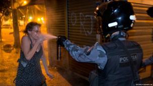 A military policeman pepper sprays a protester during a demonstration in Rio de Janeiro, Brazil