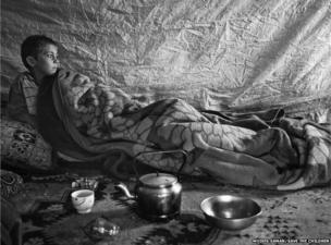 Faysal , 6, waking up inside his family's tent a settlement in the Bekaa Valley, Lebanon
