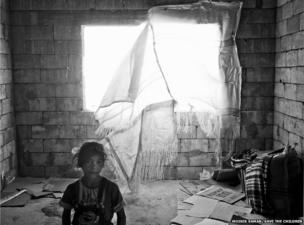 A young Syrian refugee inside her family's temporary home in an unfinished building in the Bekaa Valley, Lebanon