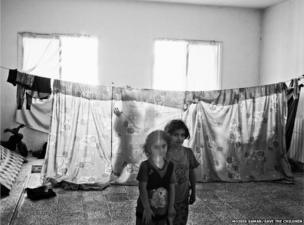 A young Syrian refugee inside her family's temporary home in an unfinished building, Bekaa Valley, Lebanon