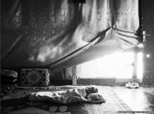 A Syrian baby sleeps inside his family's tent in the Bekaa Valley, Lebanon.