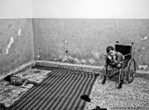 8-year-old Aziz (right) and his sister Aisha (left), both suffering from cerebral palsy, inside their family's one-room house in East Amman, an area where a large number of Syrian refugees have settled.