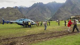 Rescuers help escort stranded pilgrims to helicopters to evacuate at Joshimath in the northern Indian state of Uttarakhand, India, Wednesday, June 19, 2013