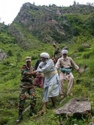 Indian army officials help travellers and villagers down a steep slope after they were stranded by the rising floodwaters of the River Alaknanda near Govindghat, Chamoli District in the northern Indian state of Uttarakhand on June 18,