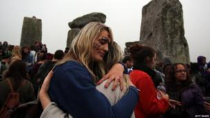 Revellers hug and cheer to mark the sunrise