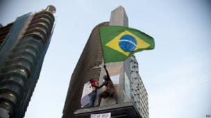 A protester waves a Brazilian flag from a building in Belo Horizonte, Brazil (20 June 2013)