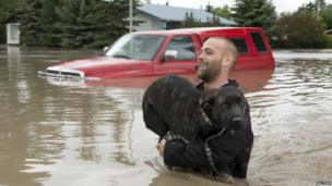 A man carries his dog to safety in High River, Alberta, Canada (20 June 2013)