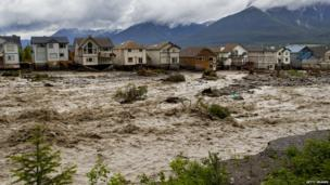 Houses damaged along the edge of Cougar Creek are shown June 20, 2013 in Canmore, Alberta, Canada. Widespread flooding caused by torrential rains washed out bridges and roads prompting the evacuation of thousands.