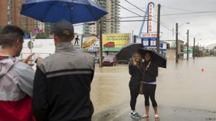 Women pose for a photo as floodwaters rise at a downtown street while evacuating during a mandatory evacuation in Calgary, Alberta June 21, 2013. The heaviest floods in decades shut down the Canadian oil capital, closing roads and bringing down bridges