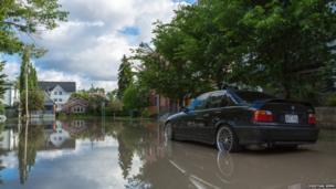 Car driving through flood waters in McDougall Road, Calgary, Canada. Photo: Christian Semm