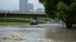 Car driving through flooded road under a bridge in Calgary, Canada. Photo: Christian Semm