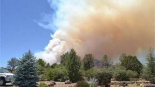 Smoke billows over the tree line in Prescott, Arizona. Julia Doyle sent this photo taken from her garden on the 18th June. Photo: Julia Doyle