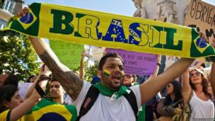 Man holds Brazil scarf above his head during a protest in Portugal. Photo: Horta do Rosário